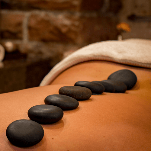 Relaxed woman receiving a hot stone massage at Hum Healing Hive